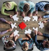 Groupe de femmes et d'hommes qui font un puzzle commun